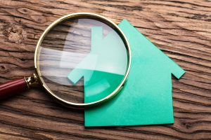 Magnifying Glass And Green Paper House