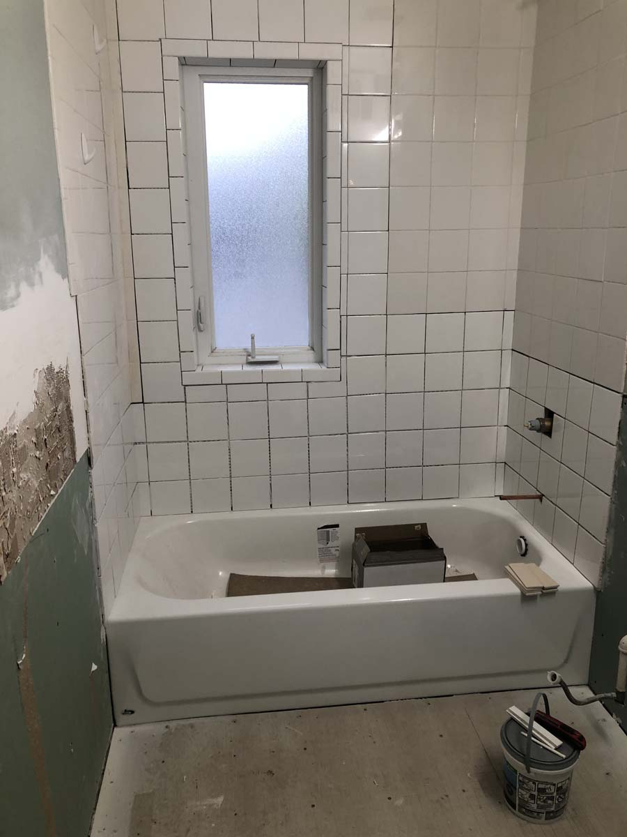 Project Note: The variance in the white wall tile is due to the age of the existing tile. The owner chose to just correct the water damaged areas and not to replace all the tile.